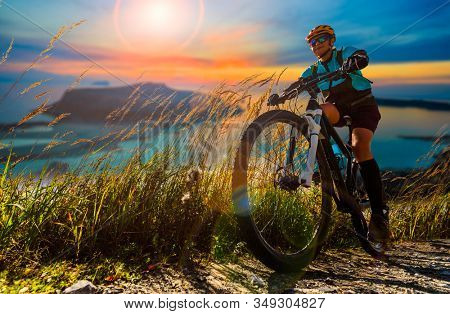 Cycling woman on electric bikes. MTB enduro trail track. Outdoor sport activity.
