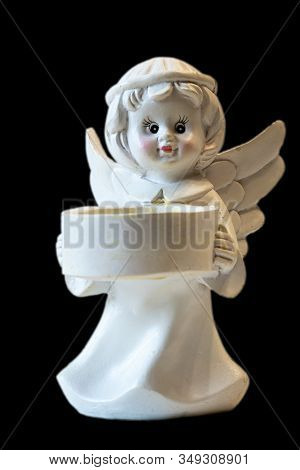 White Ceramic Angel Figurine Isolated On Black Background. Angel Figurine For Concept Design. The Co