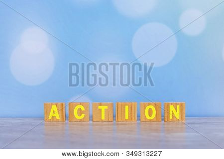 An Action Single Word On Wooden Block With Vintage Soft Blue Bokeh Background.. Business Planning An