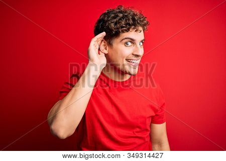 Young blond handsome man with curly hair wearing casual t-shirt over red background smiling with hand over ear listening an hearing to rumor or gossip. Deafness concept.