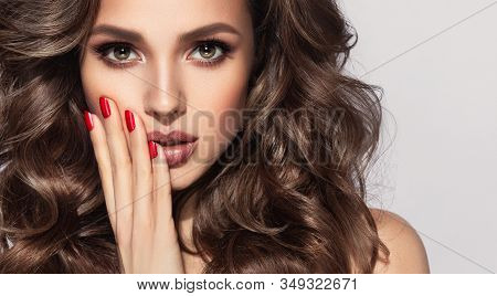 Beautiful Model With Long Curly Hair . Fashion Trend Image , The Girl With Red Manicure On Nails. Co