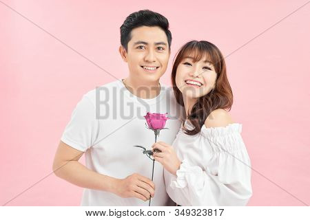 Loving Couple. Cheerful Young Loving Couple Standing Close To Each Other While Woman Holding A Red R