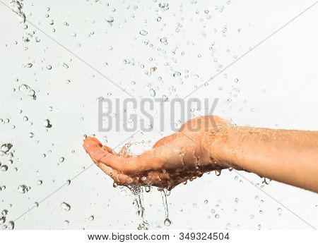 Closeup Of Drops Of Water Flowing Into Palm, Waters Splashes Scatter To Sides. Photo On White Backgr