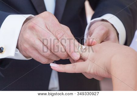 Wedding Bride And Groom Couple At Marriage Ring Vows Ceremony. Husband With Dark Suit And Wife With