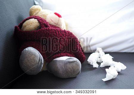 Teddy Bear Lying Sick On The Sofa Inside The House. The Concept Of Sick Children