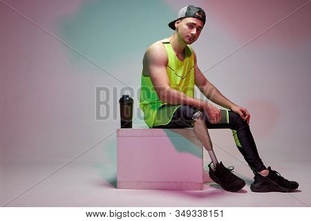 A Young Handsome Man With A Disability With A Prosthetic Leg After Training In A Gym. Fitness Clothi