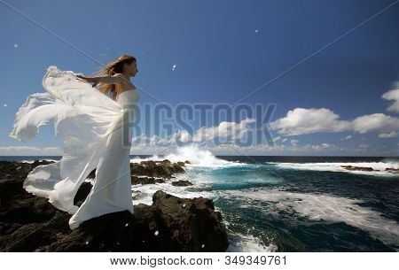 Young Elegant Bride With White Wings Of Wedding Dress On Rock Sea Shore. Side View. Ocean Waves, Spl