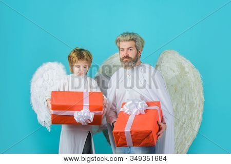 Gift Box. Happy Father In Angel Costume With Little Son Angel Holds Present. Cute Angel. Valentines