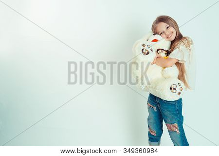 Little Girl Hugging A Teddy Bear Is Looking At The Camera. Half Body Lenght Portrait Of Caucasian Ki