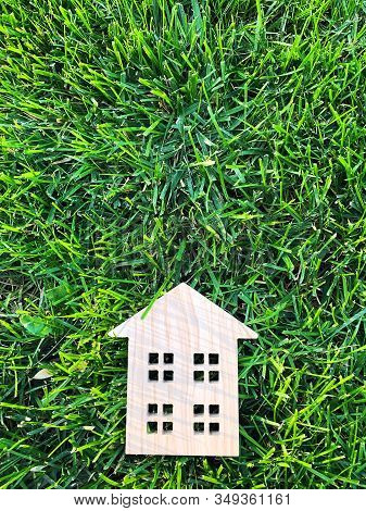 Miniature Wooden House On Green Grass. Real Estate Concept. Modern Housing. Eco-friendly And Energy
