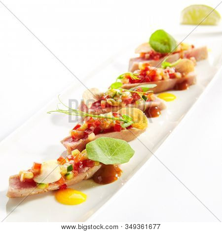 Appetizer with tuna tartar, seasonal vegetables and greens on white restaurant plate isolated. Macro photo of delicious healthy red fish tatar or tar-tar entree closeup