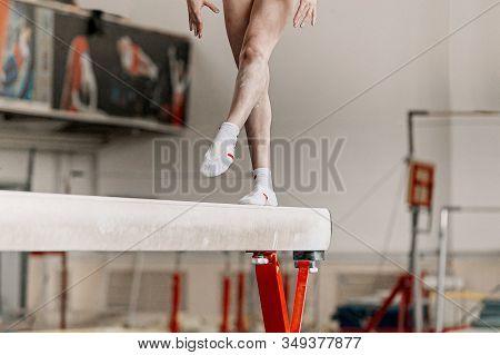 Girl Gymnast Athlete Exercise On Balance Beam In Gymnastics Gym