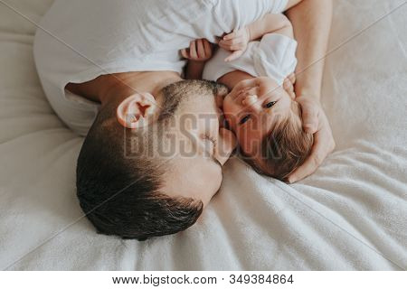 Happy Caucasian Father Lying On Bed With Newborn Baby. Man Parent Hugging Kissing Child Daughter Son