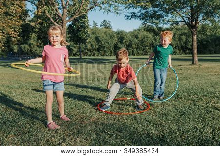 Cute Smiling Caucasian Preschool Girl Boys Friends Playing With Hoola Hoop In Park Outside. Kids Spo