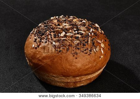 Fresh, Palatable Baked Bun Sprinkled With Sesame And Sunflower Seeds Against Black Background With C