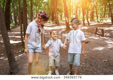 Happy Children Wearing White Shirts In Sunny Forest. Cute Girl Is Walking With Her Little Brothers H