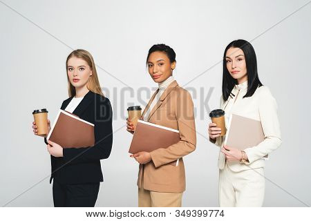 Multicultural Businesswomen Holding Disposable Cups And Folders Isolated On White