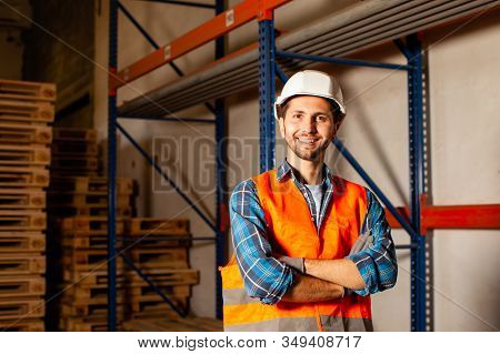 Confident Handsome Worker In Protective Hardhat And Uniform At The Warehouse Of A Industrial Manufac