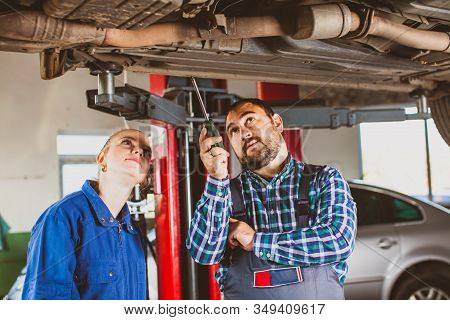 Mechanic Man Examining Car With Trainee Girl