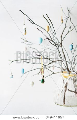 Still Life With Tree Branches Decorated With Easter Eggs, Feathers And Bunnies In A Glass Vase. Vert