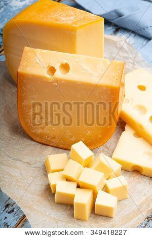Famous Hard Cheeses, Dutch Gouda And French Emmentaler In Pieces And Blocks On Paper