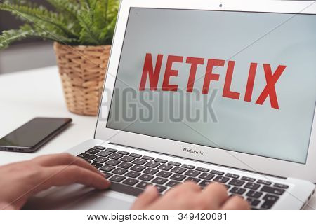 Wroclaw, Poland - Oct 23, 2019: Man With Netflix Logo On Screen. Netflix Is Most Popular Video Strea