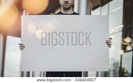 Close Up Young Man Holding Blank Canvas Placard Outdoors. Activist Protesting Against Political And