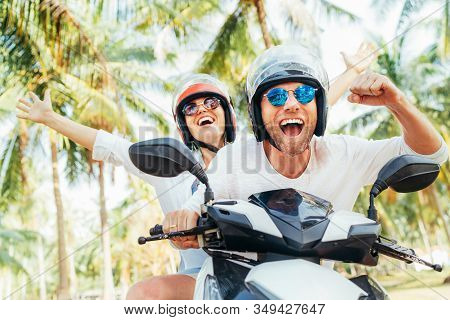 Happy Smiling Couple Travelers Riding Motorbike Scooter In Safety Helmets During Tropical Vacation U