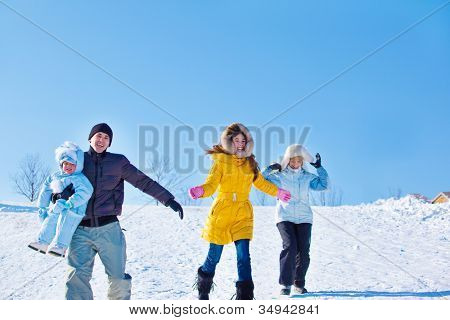 Happy people running down winter hill