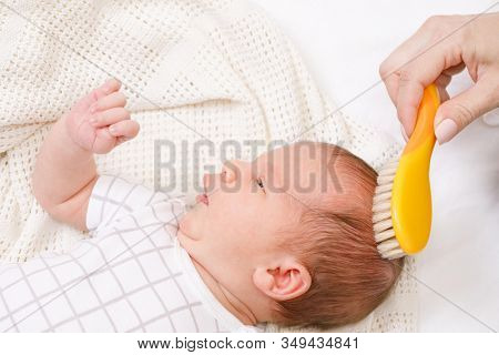 Mother brushing hair of her newborn baby using soft natural bristle hairbrush to stimulate infant's hair follicles and increase scalp blood flow for healthy hair growth