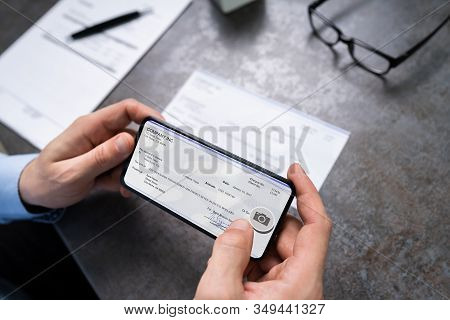 Man Taking Photo Of Cheque To Make Remote Deposit In Bank