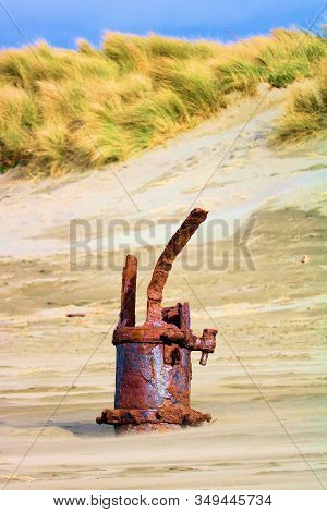 Rusty Part Of A Historic Shipwreck On The Beach Besides Sand Dunes Covered With Tallgrass Taken In T