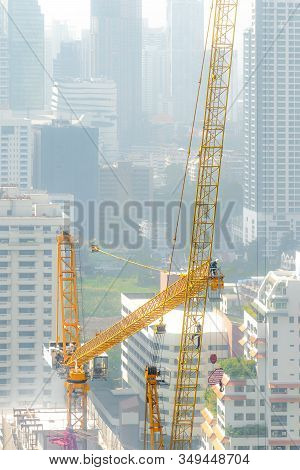 Aerial View Of A Construction Site With Building Crew Dissemble Tower Crane On A Hazy Day.