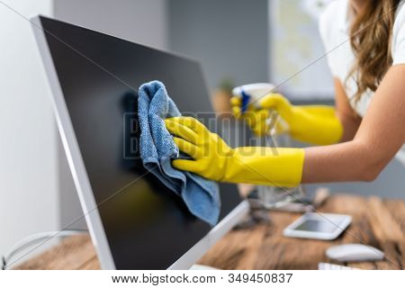 Young Worker Cleaning Desk With Rag In Office