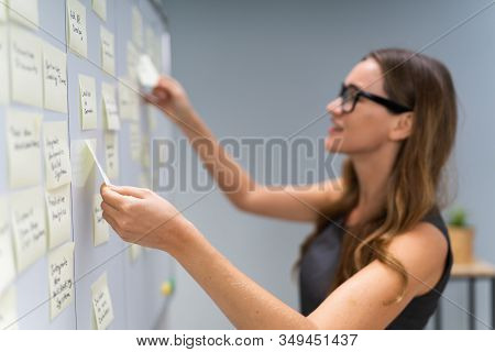 Side View Of Businesswoman Arranging Sticky Notes Attached To White Board In Office
