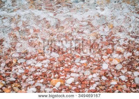 Wave On A Pebble Beach. Pink, Beige And Red Pebbles Under Clear Sea Water. The Texture Is A Pebbled