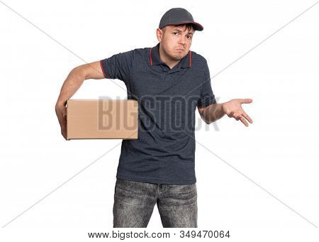 Portrait of Delivery man in cap holding cardboard box showing helpless gesture with hands - I do not know. Handsome man looking on camera. Courier making helpless sign, isolated on white background.