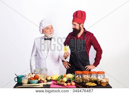 Professional Culinary. Two Chefs Stands Near Table With Vegetable. Bearded Men Chefs In Uniform. Rea