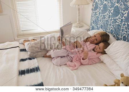 Side view of loving mother with her young daughter reading storybook in bedroom at home