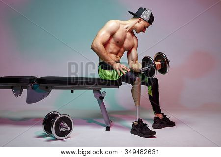 A Young Muscular Man With A Disability With A Prosthetic Leg Is Training In A Gym With Dumbbells. Mo