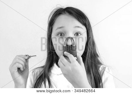 Conceptual Portrait Of A Child Keeping Silence With Lock Over Her Mouth And A Key To The Lock In You