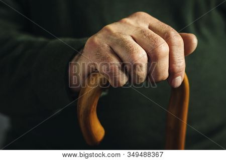 Hand Of An Old Man Highlighted In Darkness