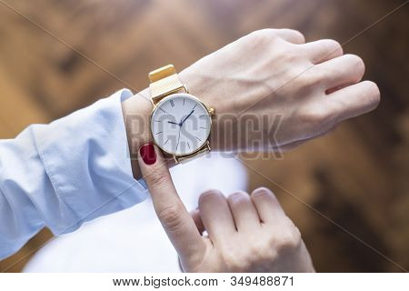 Young Woman Checking The Time On Wristwatch. Cropped Shot, Top View