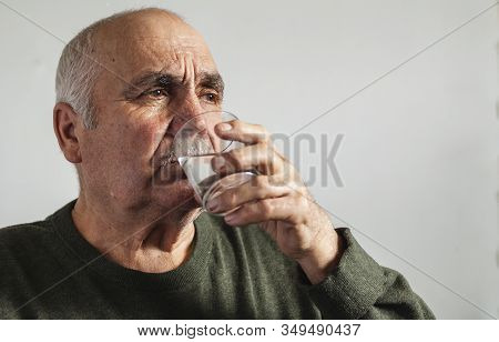 Elderly Man Taking Medication With Water In A Close Up Portrait