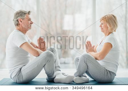 Sporty Middle Aged Couple Sitting On The Mat In The White Fitness Gym And Doing Stretching While Loo