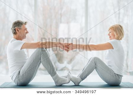Sports And Healthy Lifestyle.sporty Middle Aged Couple Sitting On The Mat In The White Fitness Gym A
