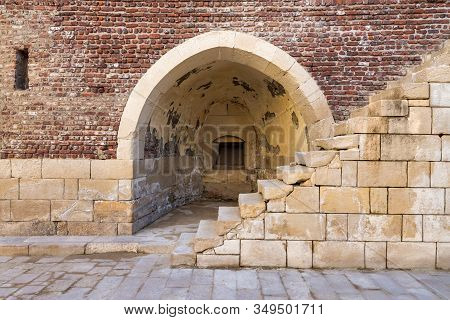 Exterior Of Ancient Brick Building With Shabby Stone Stairway And Crumbling Arched Alcove On Street