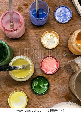 Blue, Red, Yellow, Green Pottery Glaze Liquid In Jars With Brushes On Table Top View In Pottery Stud