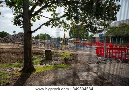 Fenced Construction Site. A Beautiful Gives Stark Contrast To The Machine And Rubble In The Backgrou