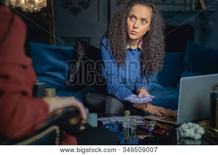 Serious Soothsayer Gazing At Her Female Client
